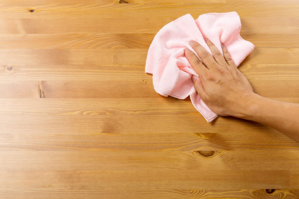 Cleaning table by pink rag